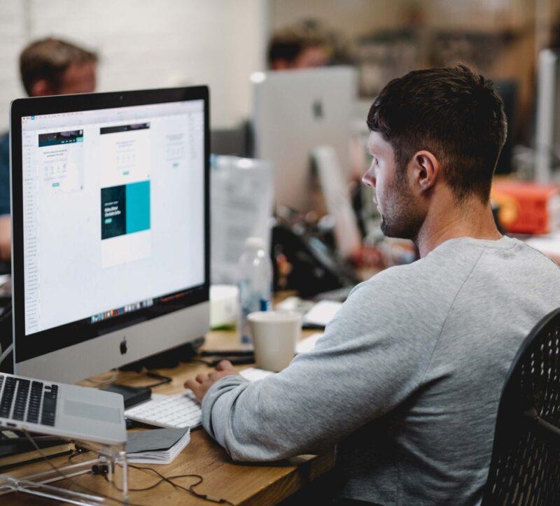 man-grey-sweatshirt-desk-office-laptop